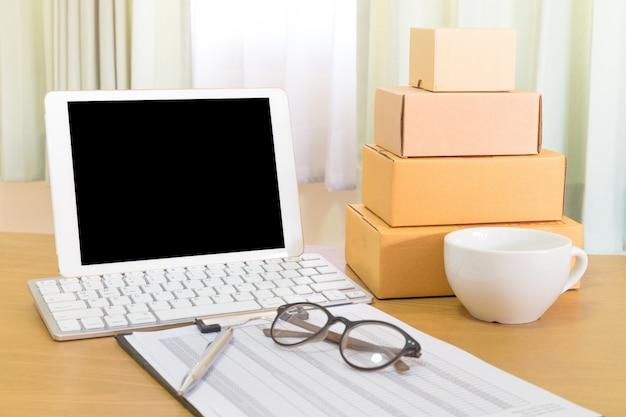 Biznesmen pracuje z telefonem komórkowym i pakuje brown pakuneczek boksuje w domu biuro. sprzedawca rąk przygotowuje produkt gotowy do dostarczenia do klienta. sprzedaż online, e-commerce rozpocznij koncepcję wysyłki.