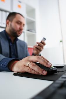 Biznesmen pracy na komputerze przytrzymaj mysz w ramię i telefon komórkowy w innym zbliżeniu