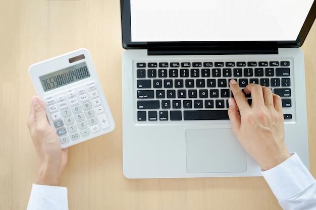 Biznesmen pracy przy komputerze i znajduje kalkulatora w biurze pracy