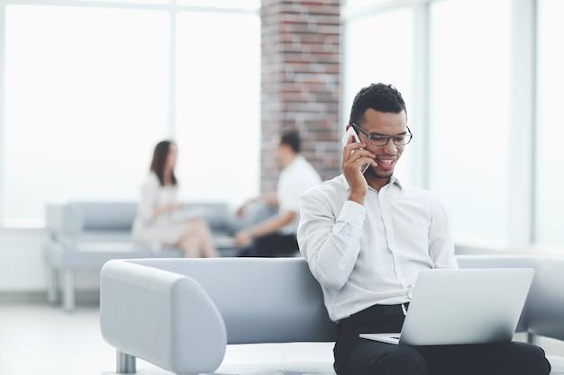 Biznesmen pracy siedzącej w holu nowoczesnego biura. ludzie i technologia