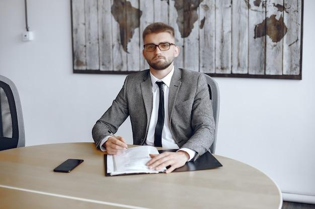 Biznesmen pracy w biurze. mężczyzna w okularach patrzy w kamerę. facet siedzi w biurze