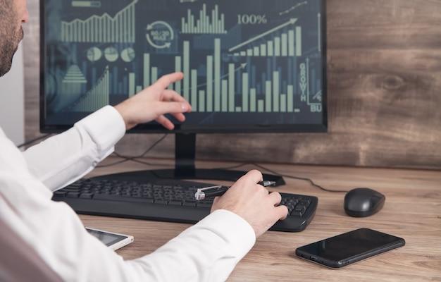 Biznesmen pracy z analizami siedzi w miejscu pracy z komputerem.