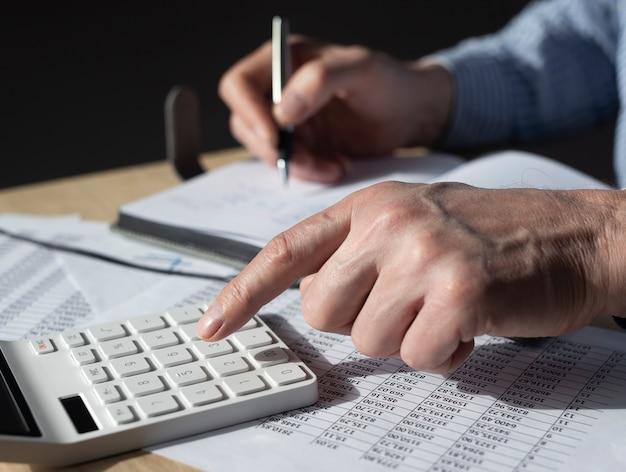 Biznesmen pracy z dokumentami finansowymi, statystyki księgowe. obliczenia podatkowe i koncepcja budżetu.