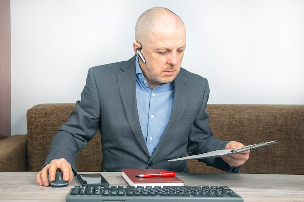 Biznesmen pracy z dokumentami w domowym biurze. kwarantanna podczas epidemii koronawirusa