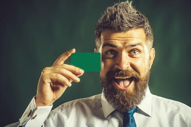 Biznesmen prezentujący biznes kartą kredytową branding poważnego brodatego mężczyzny z pustą wizytówką w