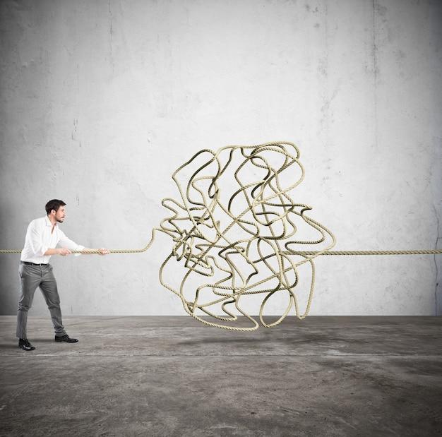Biznesmen próbuje rozwiązać skomplikowaną plątaninę