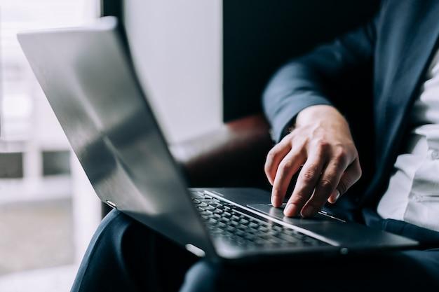 Biznesmen prowadzi rękę na klawiaturze laptopa.