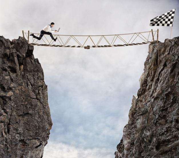 Biznesmen przebiega przez chwiejący się most, aby dostać się do flagi. cel biznesowy osiągnięcie i trudna koncepcja kariery