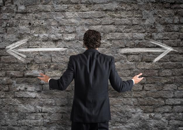 Biznesmen przed wyborem ze strzałkami w przeciwnych kierunkach