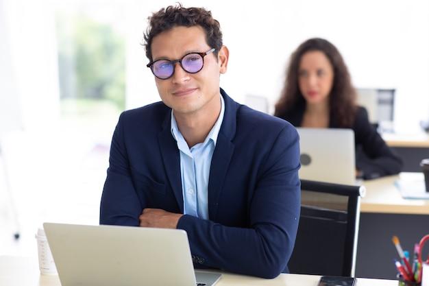 Biznesmen przedsiębiorca spojrzeć na kamery i pracy na laptopie kolega na tle w domowym biurze.
