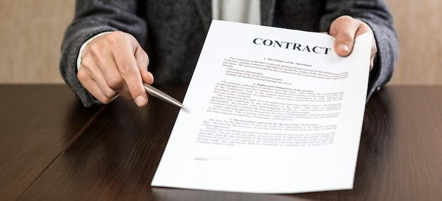 Biznesmen przekazanie umowy do podpisu, oferując długopis w ręku