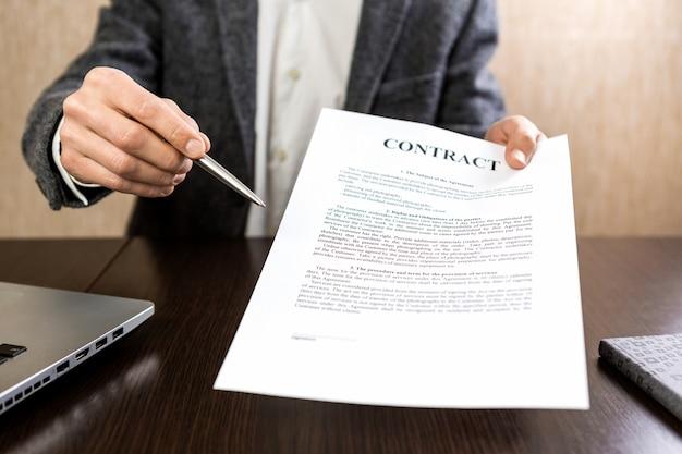 Biznesmen przekazanie umowy do podpisu, oferując srebrny długopis w ręku.