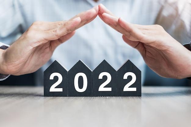 Biznesmen przekazuje 2022 szczęśliwego nowego roku z modelem domu na stole biurowym. koncepcje ubezpieczeń majątkowych i nieruchomości