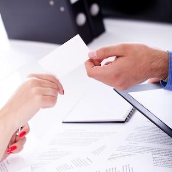 Biznesmen przekazuje wizytówkę swojemu partnerowi