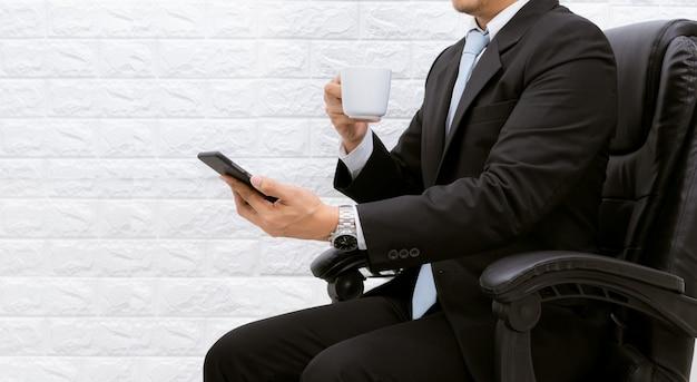 Biznesmen przerwa na kawę trzymaj smartfona wykonawczego działa zrelaksować się na laptopie przy biurku.