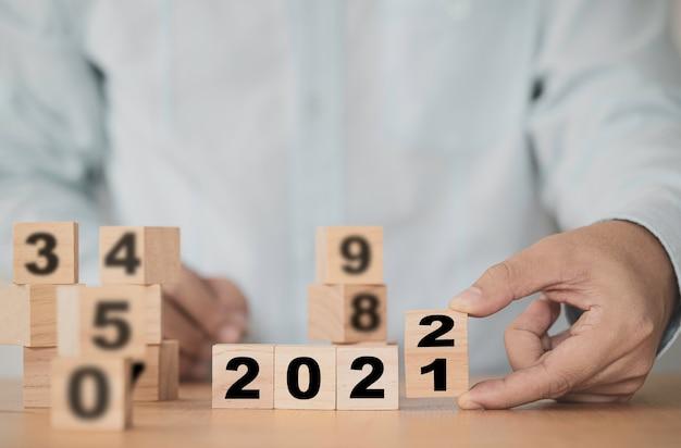 Biznesmen przerzuca rok 2021 na 2022, aby rozpocząć nowy rok biznesplan.