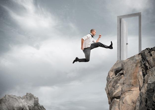 Biznesmen przeskakując góry, aby dotrzeć do drzwi. koncepcja ambicji w biznesie