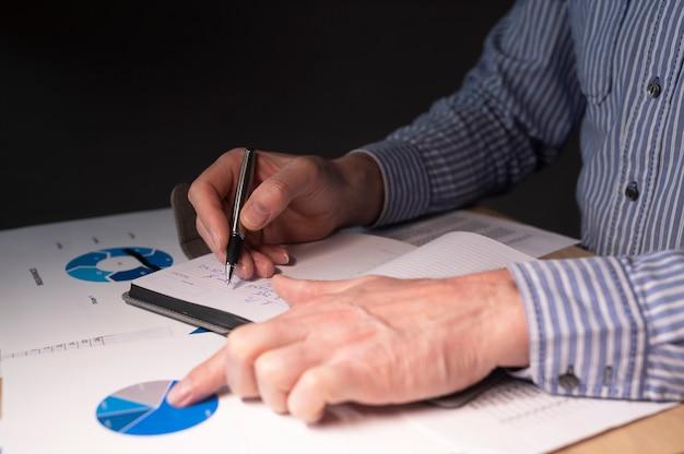 Biznesmen przy biurku z dokumentami finansowymi, przygotowanie raportu finansowego, analiza budżetu na wykresach.