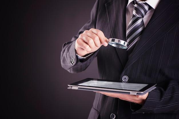 Biznesmen przy użyciu komputera typu tablet z lupą