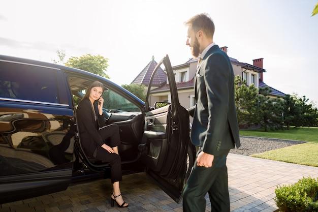 Biznesmen przyjeżdża do samochodu i otwiera drzwi dla młodej kobiety, rozmawia przez telefon. bizneswoman wysiada z samochodu i jest gotowa iść ze swoim kolegą do budynku biurowego