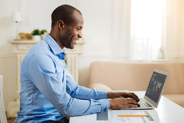 Biznesmen. przystojny szczęśliwy afro-amerykański mężczyzna uśmiecha się i pracuje na laptopie siedząc przy stole