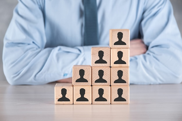 Biznesmen przytrzymaj i umieść drewniany kształt bloku kostki z ikoną użytkownika na szarym stole. miejsce na tekst. ikony internetowe interfejsu pierwszego planu. koncepcja mediów globalnej sieci, kontakt na wirtualnych ekranach, miejsce na kopię.