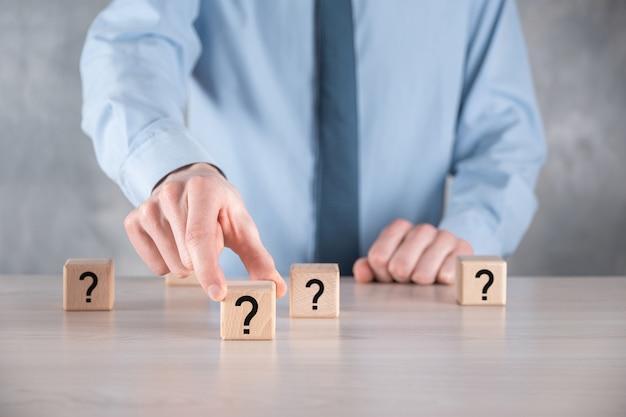 Biznesmen przytrzymaj i umieść drewniany kształt bloku kostki ze znakami zapytania na szarym stole. miejsce na tekst. koncepcja na zamieszanie, pytanie lub rozwiązanie.