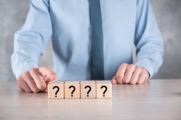 Biznesmen przytrzymaj i umieść kształt bloku drewnianego kostki ze znakami zapytania na szarym stole. miejsce na text.concept dla zamieszania, pytania lub rozwiązania.