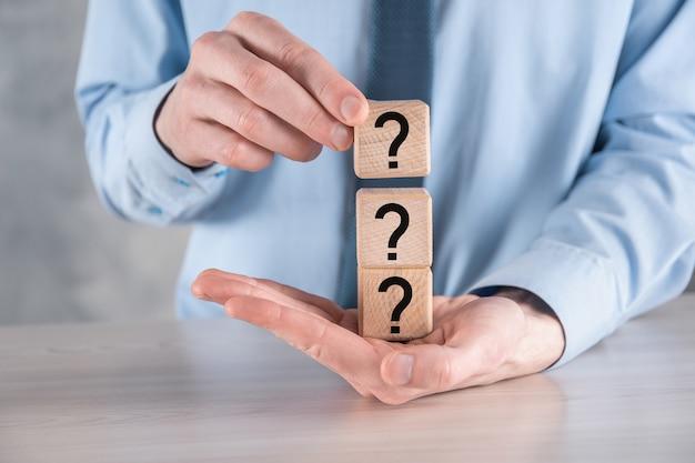 Biznesmen przytrzymaj i umieść kształt bloku drewnianego sześcianu ze znakami zapytania na szarym stole. miejsce na text.concept dla zamieszania, pytania lub rozwiązania.