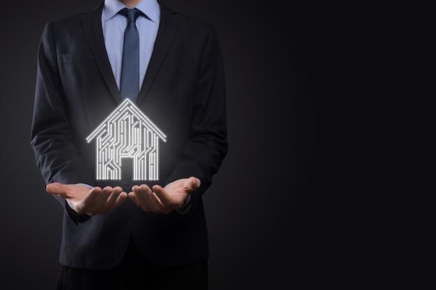 Biznesmen przytrzymaj ikonę domu. koncepcja aplikacji inteligentnego domu sterowanego, inteligentnego domu i automatyki domowej. projekt pcb i osoba z inteligentny telefon. koncepcja sieci internet technologii innowacji.