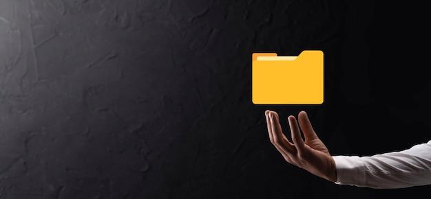 Biznesmen przytrzymaj ikonę folderu. system zarządzania dokumentami lub konfiguracja dms przez konsultanta it z nowoczesnym komputerem wyszukują zarządzanie informacjami i plikami firmowymi. przetwarzanie biznesowe,