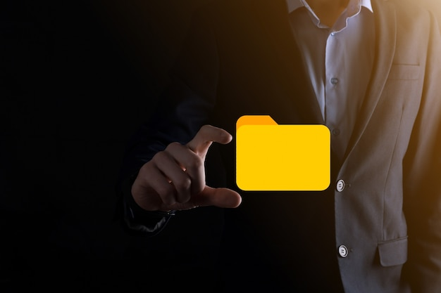 Biznesmen przytrzymaj ikonę folderu. system zarządzania dokumentami lub konfiguracja dms przez konsultanta it z nowoczesnym komputerem wyszukują zarządzanie informacjami i plikami firmowymi. przetwarzanie biznesowe