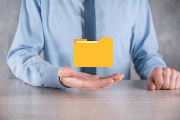 Biznesmen przytrzymaj ikonę folderu. system zarządzania dokumentami lub konfiguracja dms przez konsultanta it z nowoczesnym komputerem wyszukuje zarządzanie informacjami i plikami korporacyjnymi. przetwarzanie biznesowe.