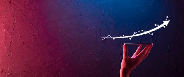 Biznesmen przytrzymaj rysunek na ekranie rosnącego wykresu, strzałka ikony pozytywnego wzrostu. wskazując na wykres kreatywnego biznesu ze strzałkami w górę. finanse, koncepcja rozwoju biznesu