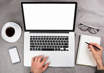 Biznesmen ręka używać cyfrowego pastylki writing na ślimakowatym notepad nad popielatym biurkiem