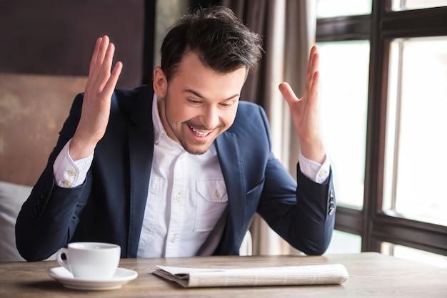 Biznesmen radosna gazeta do czytania z filiżanką kawy.