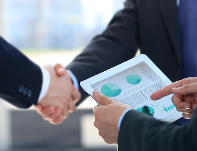 Biznesmen ręce dotykając cyfrowy tablet puste miejsce na ekranie, uścisk dłoni podczas spotkania.
