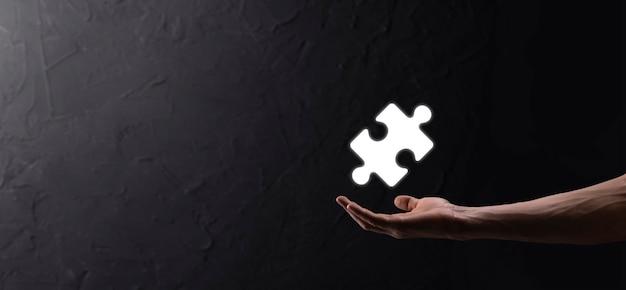 Biznesmen ręce łączące elementy układanki reprezentujące połączenie dwóch firm lub joint venture, partnerstwo, fuzje i koncepcja przejęcia.