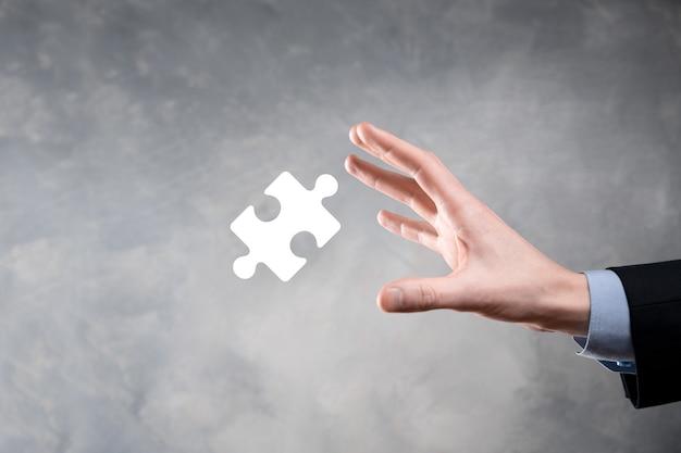 Biznesmen ręce łączące elementy układanki reprezentujące połączenie dwóch firm lub joint venture, partnerstwo, koncepcję fuzji i przejęć