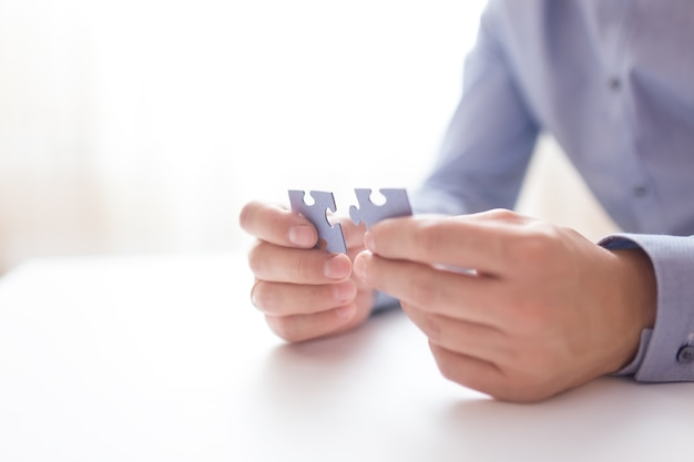 Biznesmen ręce łączące puzzle.