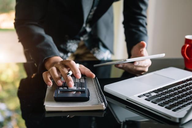 Biznesmen ręce pracy z finansami o kosztach i kalkulator i laptop z tabletem, smartfonem w biurze w świetle poranka