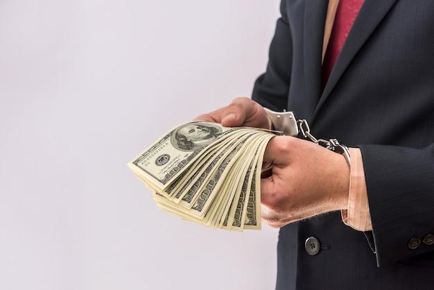 Biznesmen ręce trzymają dolarów więźniów w kajdankach. pojęcie przestępczości korupcyjnej i przekupstwa