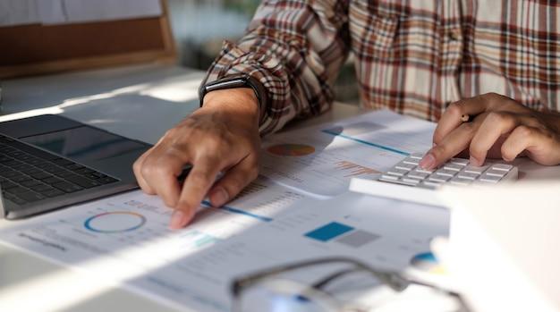 Biznesmen ręce trzymając pióro działa na kalkulatorze i dokumentacji finansowej.
