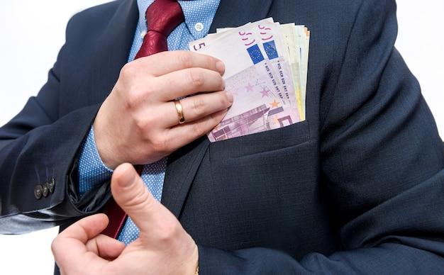 Biznesmen ręce ukrywanie banknotów euro w kieszeni