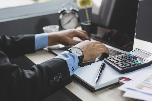 Biznesmen ręce wpisując klawiaturę na laptopie