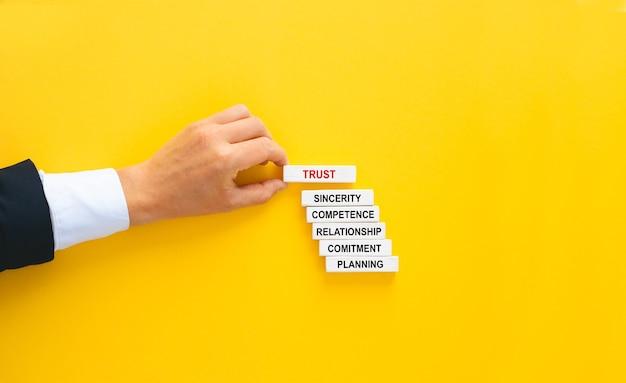 Biznesmen ręcznie buduje drewniane bloki z koncepcją zaufania.