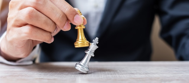 Biznesmen ręcznie przenoszenie złota figura szachowego króla i szach-mat enermy lub przeciwnika podczas konkursu szachownicy. koncepcja strategii, sukcesu, zarządzania, planowania biznesowego, przerwy i przywództwa