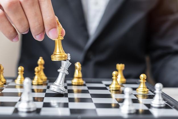 Biznesmen ręcznie przenoszenie złota figura szachowego króla i szach-mat enermy lub przeciwnika podczas konkursu szachownicy.