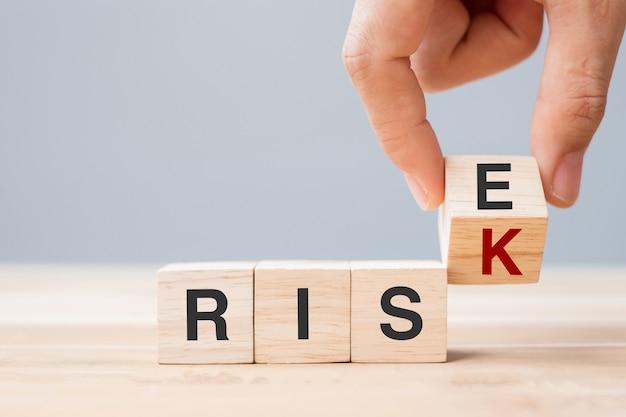 Biznesmen ręcznie przerzucanie drewnianych bloków kostki z ryzykiem zmiany na tekst na tle tabeli. koncepcje ekonomiczne, szansa, postawa, szansa i kryzys