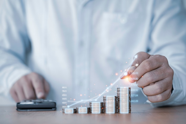 Biznesmen ręcznie rysuje wirtualny rosnący wykres z układaniem monet pieniężnych, zyskiem z inwestycji biznesowych i dywidendą depozytową oszczędzającą wzrost w koncepcji 2021.